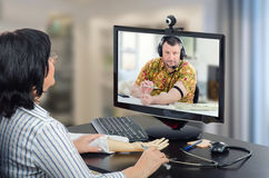 Online doctor cares male patient. Virtual female doctor has just explained how to make an intravenous injection with training arm and now oversees telehealth Stock Photo
