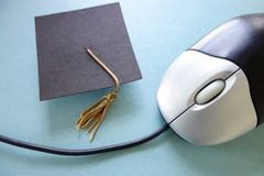 Online education. Closeup of a computer mouse and graduation cap - online education concept Stock Images