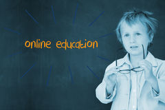 Online education against schoolboy and blackboard Royalty Free Stock Photos