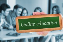 Online education against smiling friends students using laptop. The word online education and hand showing chalkboard against smiling friends students using Stock Photos