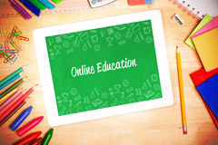 Online education against students desk with tablet pc Royalty Free Stock Photo