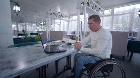 Online education, student disabled man on wheelchair uses modern laptop technology to learn from online lessons and