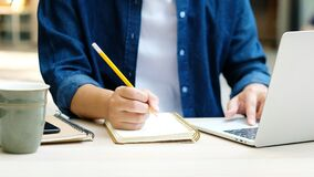 Free Online Education Learning, Work From Home, Man Hand Writing On Notebook While Using Laptop Computer, Adult Male Student Study Stock Photo - 177445400