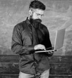 Online education. Modern technology education. Hipster teacher wear eyeglasses and necktie holds laptop. Digital. Technology education. Teacher bearded man with stock photos