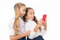 Online entertainment concept. Schoolgirls use smartphone check social networks. Send message friend. Online. Communication. Send selfie social network. Grimace royalty free stock images