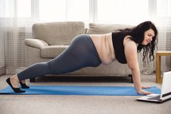 Obese woman working out with online personal couch. Online fitness class, home training, technology and diet. overweight woman doing plank under the supervision royalty free stock photo