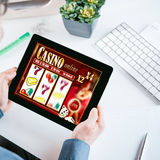 Online gambler gambling at the office. Holding his tablet computer showing a casino interface with lucky numbers above his desk and workspace stock photos