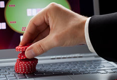 Online gambling. Player placing chips on a laptop which shows an online casino - online gambling concept; focus on the chips royalty free stock image