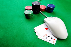 Online Gambling Concept. Online gaming and gambling concept, green felt, a mouse and cards royalty free stock photos