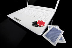 Online gambling concept. Gambling chips and cards on white laptop computer royalty free stock image
