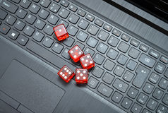 Online gambling. Five red casino dice over the laptop keyboard Stock Photo