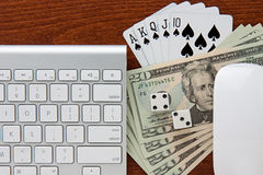 Online Gambling. Keyboard and mouse frame twenty dollars bills with two dice and space royal flush cards on desktop royalty free stock images