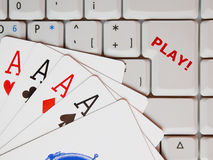 Online gaming. Poker aces and computer keypad with enter key replaced with text Play! as a concept of on-line gaming Royalty Free Stock Photos