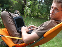 Online in the garden. Young man in deckchair with netbook stock photo