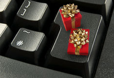 Online gift shopping. Online gifts, such as for christmas or birthdays, with gold bows on top of a computer enter key Stock Photo
