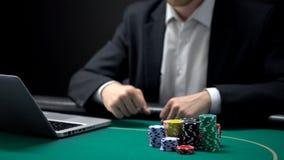 Online gokker die met dichtgeklemde vuisten op weddenschappenresultaten wachten voor laptop stock afbeeldingen