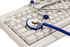 Online Health Advice. Blue stethoscope on computer keyboard. Shadows under stethoscope and keyboard are intentional. White background. Color image stock photography