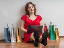 Online het winkelen concept De jonge mooie vrouw zit op vloer thuis en gebruikt laptop voor het winkelen Stock Afbeelding