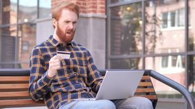 Online het winkelen mislukking voor de jonge mensenzitting van de roodharigebaard op bank stock videobeelden