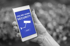 Online home security concept on a smartphone. Female hand holding a smartphone with online home security concept stock photos