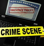 Online Identity Theft. Social Security card with Identity Theft stamp on laptop screen with crime scene tape royalty free stock image