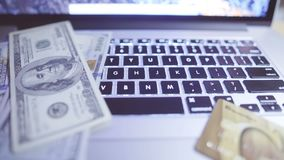 Online investments concept. Online investments. Sliding video of laptop keyboard with US dollars and credit card stock video footage