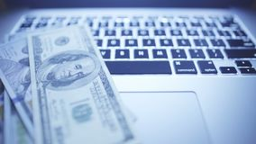 Close-up of laptop keyboard. Online investments. Sliding video of laptop keyboard with US dollars stock video