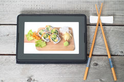 Online Japanese food delivery concept. With sushi rolls on an electronic tablet and chopsticks Royalty Free Stock Images