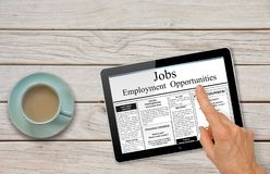 Online job hunting Hand with computer tablet reading employment ads on table with coffee royalty free stock photo