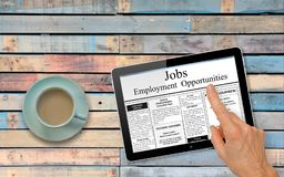 Online job hunting Hand with computer tablet reading employment ads on table with coffee stock images