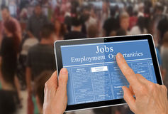 Online job hunting Hands with computer tablet reading employment ads infront of crowd of people. Focus on foreground - computer tablet reading employment ads in stock photos