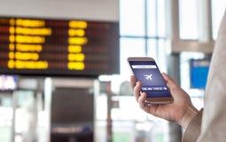 Online- kontrollera in med mobiltelefonen i flygplats royaltyfri fotografi