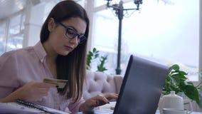 Online kopend, betaalt het gelukkige studentenmeisje onderwijs door creditcard en laptop computer na de zitting van de afstandsst stock video