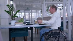 Online-kurser, den student lamslog mannen i rullstol använder en bärbar dator och drickakaffe som sitter på tabellen med böcker i arkivfilmer