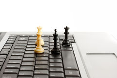 Online laptop chess. Chess pieces on a laptop or notebook computer depicting on line gaming Royalty Free Stock Photos