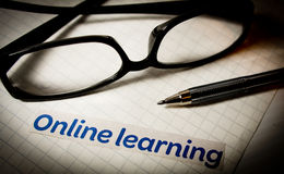Online learning. With glasses and a pen on graph paper Royalty Free Stock Photography