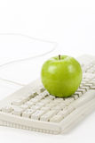 Online learning. Green apple and computer keyboard, concept of online learning Stock Image