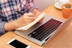 Online learning course concept. student using computer laptop for training online course and writing lecture note in notebook.