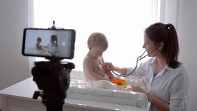 Online lecture, blogger family doctor with baby examining little patient using stethoscope and leads live learning stock footage