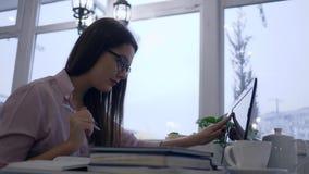 Online lerend, gebruikt het studentenmeisje laptop en schrijft nota's in notitieboekjezitting bij lijst in koffie op achtergrond  stock footage