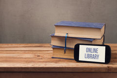 Online library concept with smart phone and old books on wooden table Stock Image