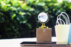 Online market place, E-commerce,fast trading concept : Colorful. Shopping bags, Paper carton with crystal globe and on tablet depicts customers order things stock photo