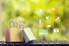 Online marketing/payment concept: shopping bags with smartphones on computer keyboard, icon online shopping and social media