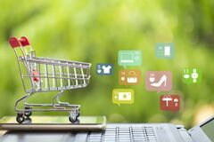 Online marketing and payment concept: Shopping cart with smartphone on laptop computer and icon online shopping and social media