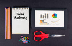 Online Marketing.Tablet, pencils, scissors, paper clips and note. Pad on the table Stock Photos