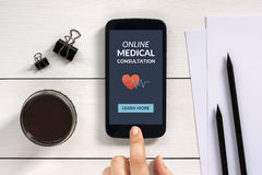 Online medical consultation concept on smartphone screen with of. Fice objects on white wooden table. All screen content is designed by me Royalty Free Stock Image