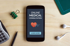 Online medical consultation concept on smartphone screen on wood Royalty Free Stock Photos