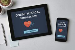 Online medical consultation concept on tablet and smartphone scr. Een over gray table. All screen content is designed by me. Flat lay Stock Images