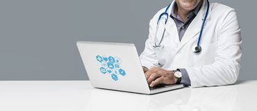 Online medical consultation. Professional  doctor sitting at office desk and working with a laptop, online medical consultation and technology concept Royalty Free Stock Image