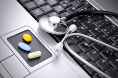 Online medicine. Stethoscope and pills on the computer royalty free stock images